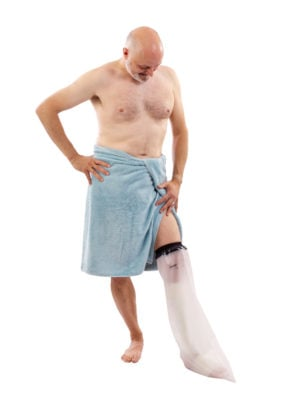 Man in a blue towel looking at his left leg wearing a LimbO Waterproof Protector