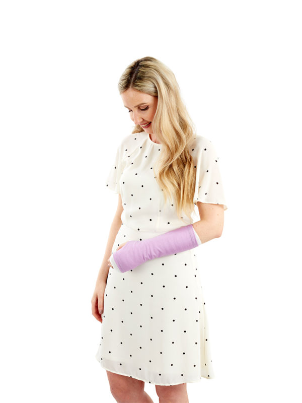 A woman standing up and wearing a purple coloured LimbO Arm Cast Sleeve on her left arm.