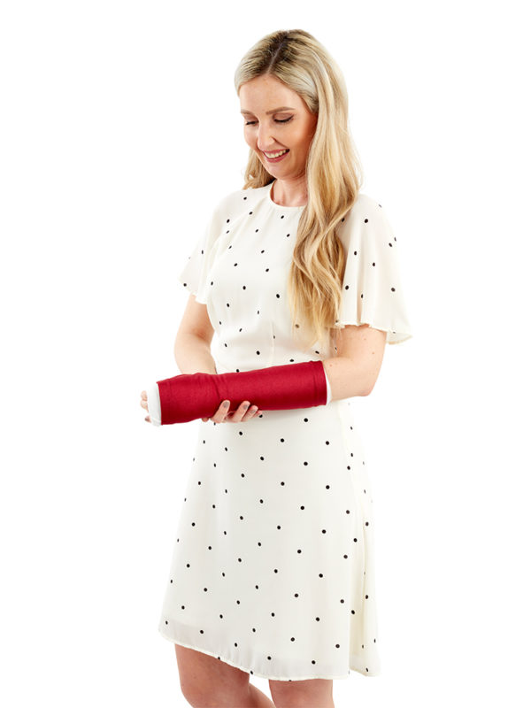 A woman standing up and wearing a red coloured LimbO Arm Cast Sleeve on her left arm.