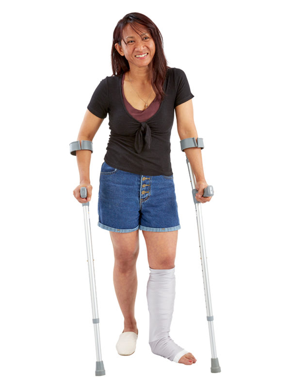 Woman standing on crutches wearing a LimbO Leg Cast Sleeve on her left leg