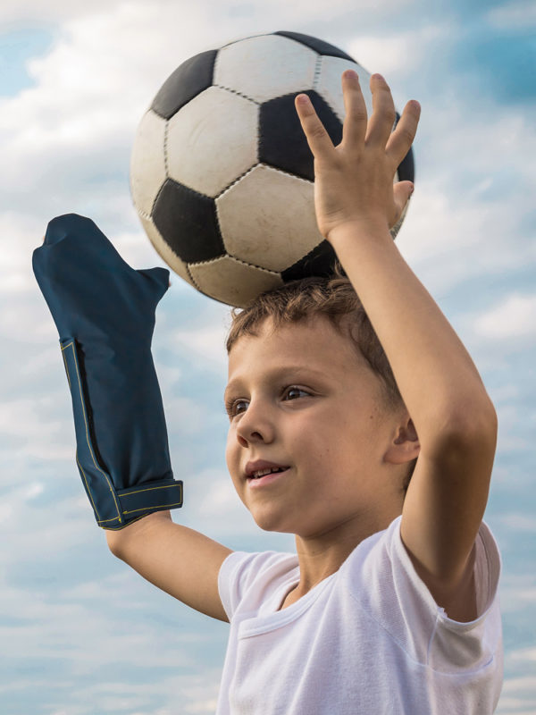 Young boy wearing an Outcast Child Arm Outdoor Weather Protector on his right arm and holding a football above his head