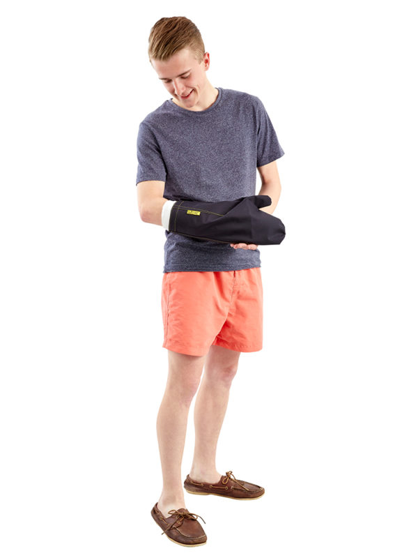 Young man wearing an Outcast Adult Arm Outdoor Weather Protector Mitt, looking at his arm