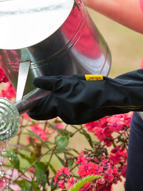 Person holding watering can wearing an outcast outdoor arm weather protector
