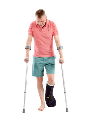 A man standing up on crutches, wearing an Outcast Weatherproof Foot Protector on his left foot.