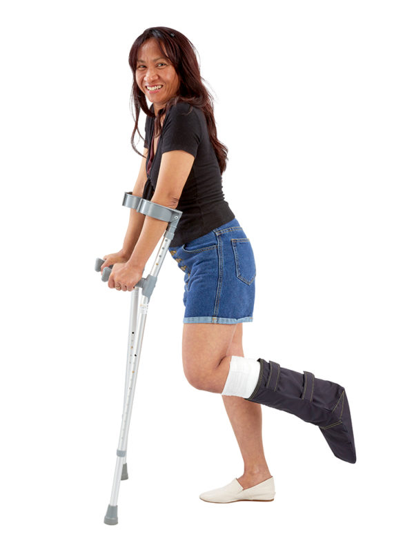 Lady on crutches, smiling and wearing an Outcast Foot Outdoor Weather Protector on her left leg
