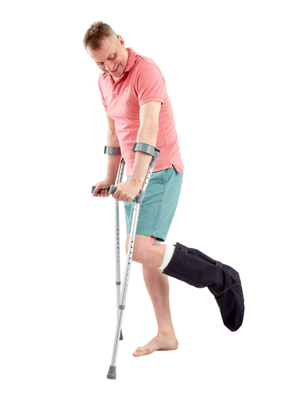 Man on crutches smiling, wearing an Outcast Foot Outdoor Weather Protector on his left foot