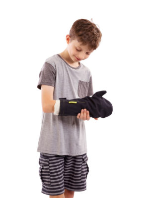 Young boy standing up and wearing an Outcast Child's Arm Weatherproof Protector on his right arm, covering a cast or dressing.