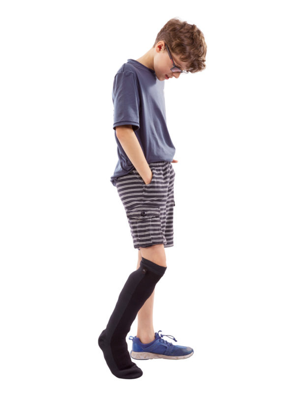 A young boy standing up and wearing a Sealskinz Child's Leg Outdoor Cover on his right leg