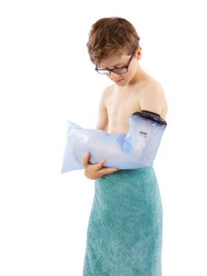 Boy wearing a towel around his waist and a LimbO Child's Full Arm cast protector on his left arm