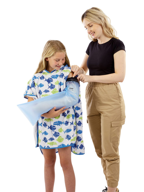 Girl wearing a LimbO child's full arm cast protector, standing with her Mum who is helping apply the waterproof seal of the product