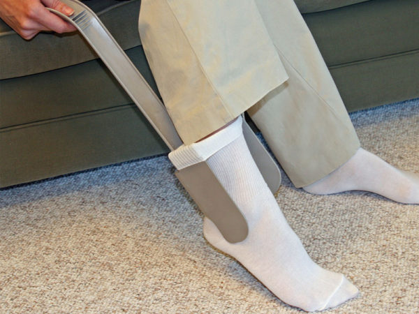 A close up of a person sitting down with their foot wearing a sock using the Sock Aid Sock Horse.