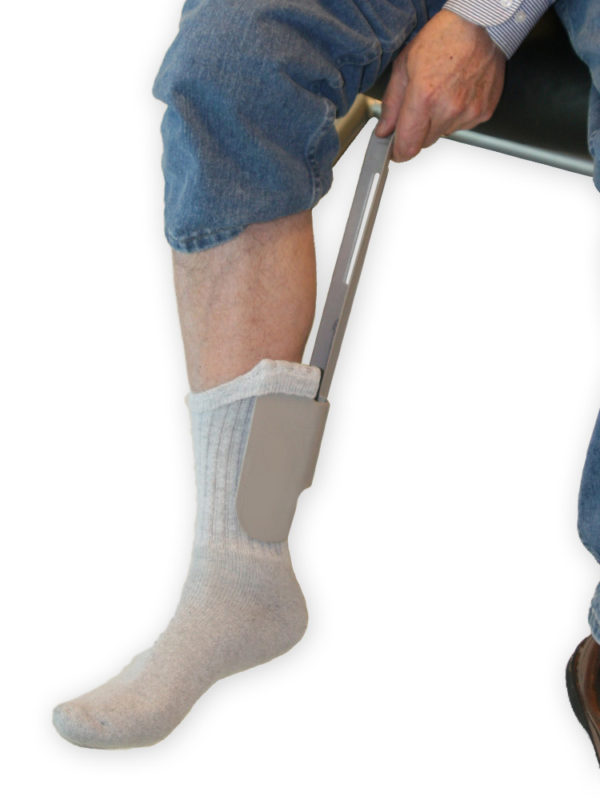 A gentleman sitting down and putting his foot into a sock using a Sock Aid Sock Horse.