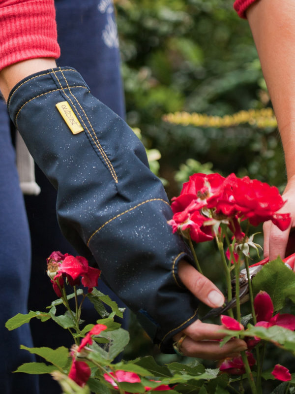 A woman wearing an Outcast Arm Cast Outdoor Weather Protector on her right arm whilst touching flowers outside