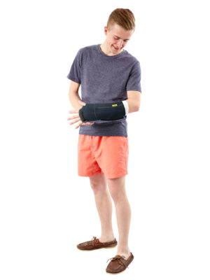 A young man standing up and looking at his left arm which is wearing a blue Outcast Adult Arm Cast Outdoor Weather Protector - Fingers Free version.