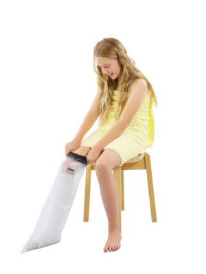 Young girl sitting down and wearing a LimbO half leg cast protector on her right leg