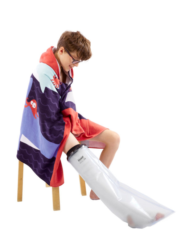 Boy in a towel, sitting on a stool whilst wearing a LimbO Child's Full Leg Waterproof Protector on his right leg