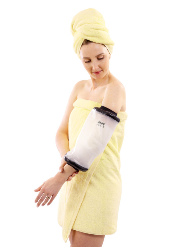 A woman in a yellow towel standing up and wearing an Extra Slim M45 LimbO Waterproof Protector on her left elbow.