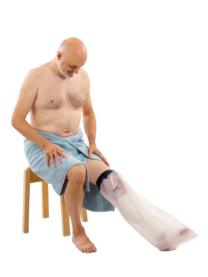 Man in a blue towel sitting on a stool and wearing a half leg LimbO Waterproof Protector on his left leg