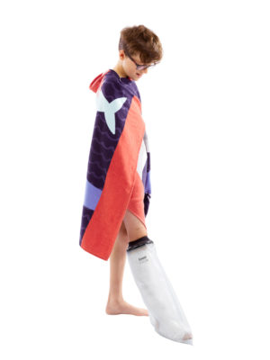 Young boy standing up in a towel and wearing a LimbO Child's Half Leg Cast Waterproof Protector on his right leg