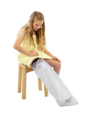 Young girl sitting down in a yellow towel wearing a Child's Full Leg Cast Waterproof Protector on her right leg
