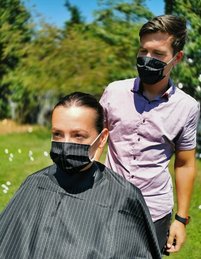 Young lady sitting down wearing a barber cape and a black pinstripe coloured Neocape Reusable Face Mask on her face