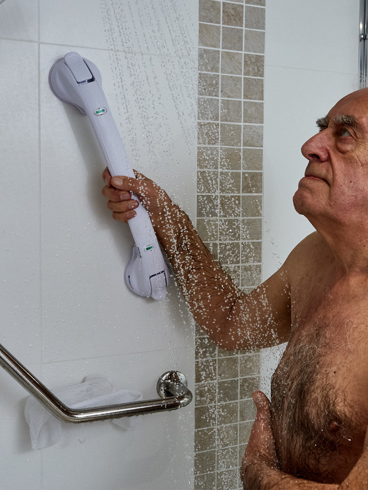 An elderly man grabbing a Stick and Stay Grab Handle with his right hand whilst washing in the shower